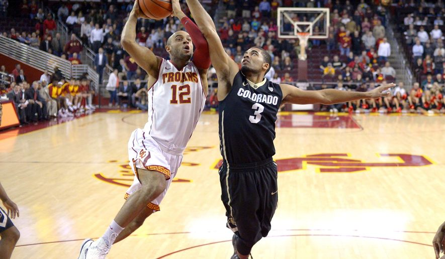 Southern California guard Julian Jacobs, left, shoots as Colorado guard Xavier Talton defends during the first half of an NCAA college basketball game Wednesday, Feb. 17, 2016, in Los Angeles. (AP Photo/Mark J. Terrill)