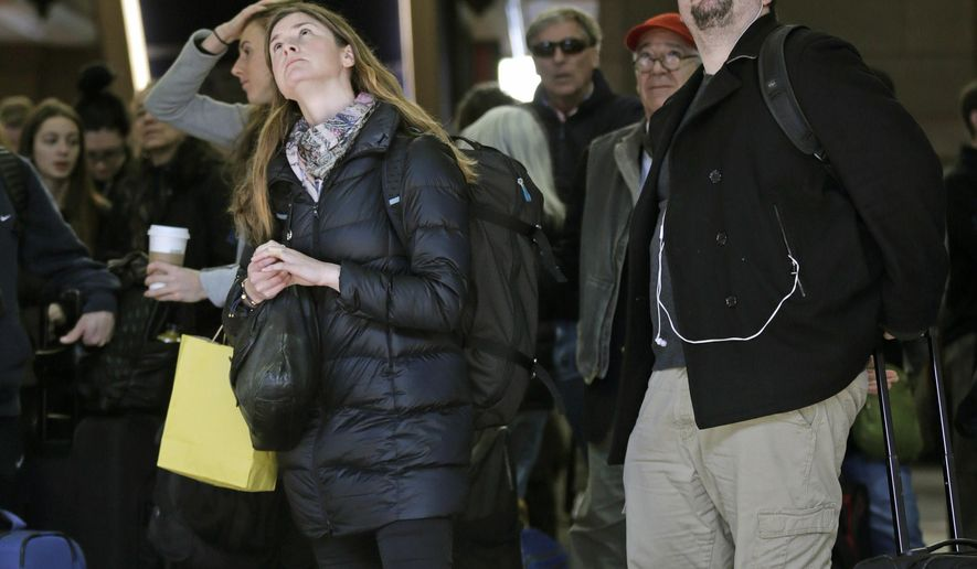 With many delays and cancelations posted, travelers watch the train departure board at South Station in Boston, Thursday, Feb. 18, 2016. Amtrak warned travelers of delays due to a signal problems at South Station.  Engineers are working to fix the malfunction, significantly limiting the number of trains entering and leaving Boston, according to Amtrak. (AP Photo/Charles Krupa)