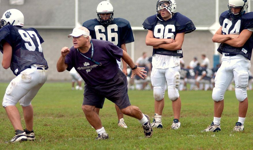 FILE - In this Aug. 16, 2004, file photo, Berwick High School football coach George Curry, second from left, demonstrates techniques during blocking and tackling drills at Crispin Field in Berwick, Pa. Curry, whose 455 victories over a 46-year career are the most by a Pennsylvania high school football coach, was diagnosed midway through the 2015 football season with Lou Gehrig's disease, also called amyotrophic lateral sclerosis or ALS. The players, from left, are Seth Fetterolf, Nick Corridini, Jake Fetterolf and Keith Ball. (Bill Hughes/Bloomsburg Press Enterprise via AP, File) MANDATORY CREDIT