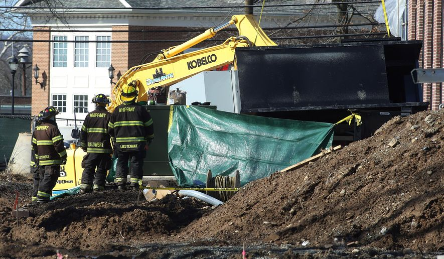 Police, firefighters and rescue workers work the scene of a construction accident involving a crane and a fallen generator at the future home of the Whippany Fire Company in Hanover, N.J., Thursday, Feb. 18, 2016. A five-ton generator fell from a crane at the construction site in northern New Jersey, killing at least one worker and severely injuring another. (Bob Karp/The Daily Record via AP) MANDATORY CREDIT