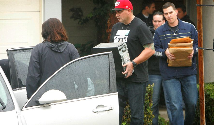 FBI and Homeland Security investigators carry a computer tower and manila envelopes from the Corona, Calif.,  home of Syed Raheel Farook while executing a search warrant at the home on Thursday, Feb. 18, 2016. FBI agents on Thursday were searching the California townhome of the brother of one of the shooters in the San Bernardino terror attack. Syed Raheel Farook is a Navy veteran who earned medals for fighting global terrorism. (Stan Lim /The Press-Enterprise via AP)  MAGS OUT; MANDATORY CREDIT; LOS ANGELES TIMES OUT