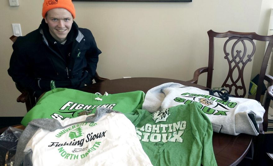In this Feb. 9, 2016 photo provided by Marlys Lord Carlson, University of North Dakota freshman Nick Carlson smiles over his haul of UND Fighting Sioux gear that he bought at Ralph Engelstad Arena in Grand Forks, N.D. The merchandise is part of the Dacotah Legacy Collection that includes a limited number of items featuring the nickname that was retired more than three years ago after the NCAA deemed the logo hostile and abusive. Most of the items sold out in one day. (Marlys Lord Carlson /Marlys Lord Carlson Photography via AP)