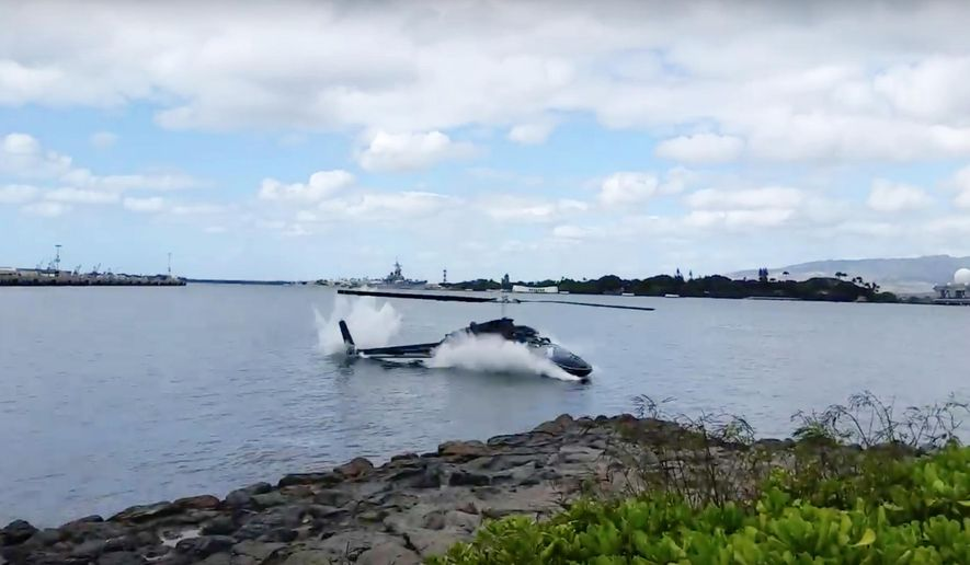 In this image taken from video provided by Shawn Winrich, a helicopter crashes near Parl Harbor, Hawaii on Thursday, Feb. 18, 2016. The private helicopter with five people aboard crashed and sunk into the water, leaving a teenage passenger in critical condition. (Shawn Winrich via the AP)