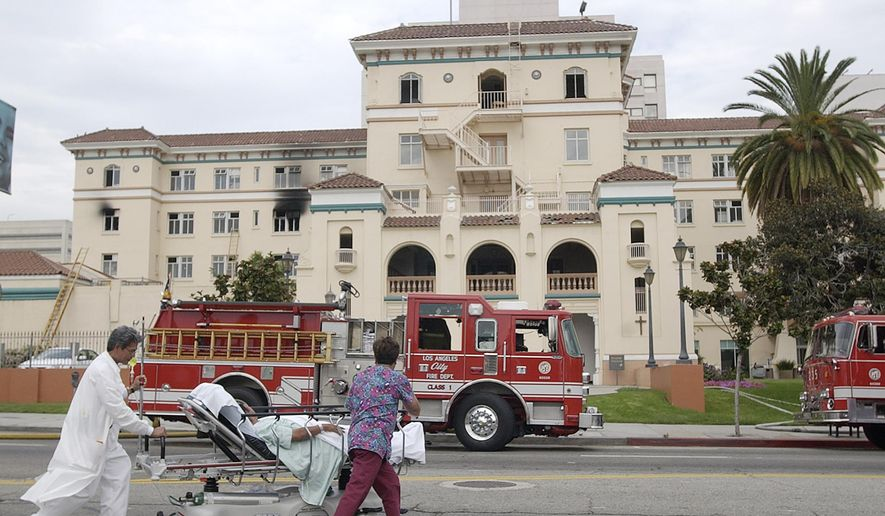 "FILE - In this July 22, 2003, file photo, nurses evacuate a patient after a fire broke out on the third floor of the 434-bed the formerly named Queen of Angels-Hollywood Presbyterian Medical Center, with visibly blackened windows, in the Hollywood section of Los Angeles. The FBI said Wednesday, Feb. 17, 2016, it is investigating a computer network extortion plot at the Los Angeles hospital. In the attacks known as ""ransomware,"" hackers lock up an institution's computer network and demand payment to reopen them. FBI spokeswoman Laura Eimiller said Wednesday that the agency is investigating such a plot at the Hollywood Presbyterian Medical Center. (AP Photo/Nick Ut, File)"