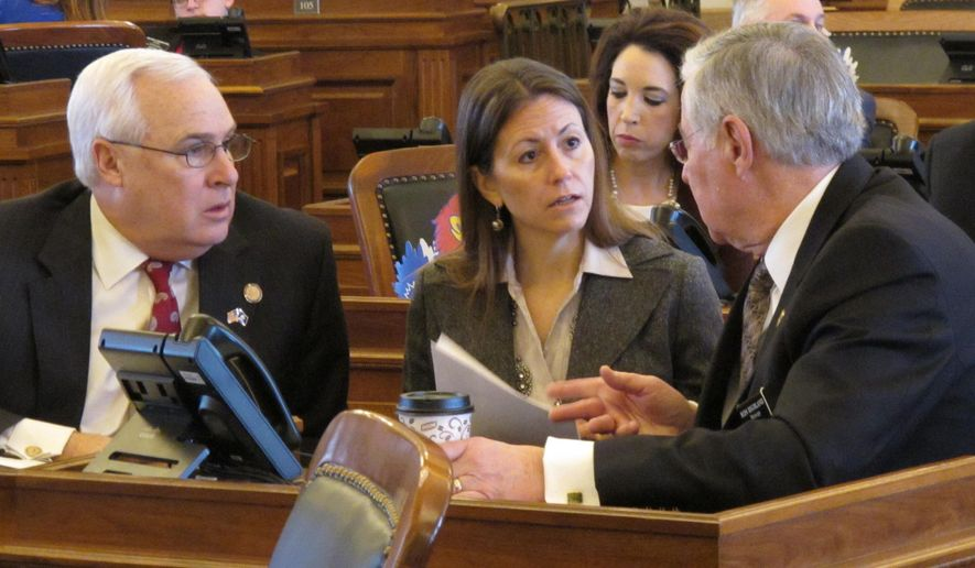Kansas state Reps. Jerry Lunn, from left, R-Overland Park, and Kasha Kelley, R-Arkansas City, confer with House Education Committee Chairman Ron Highland, R-Wamego, during the chamber's session, Thursday, Feb. 18, 2016, at the Statehouse in Topeka, Kan. The Education Committee has approved a bill to repeal the state's Common Core academic standards for public schools. (AP Photo/John Hanna)