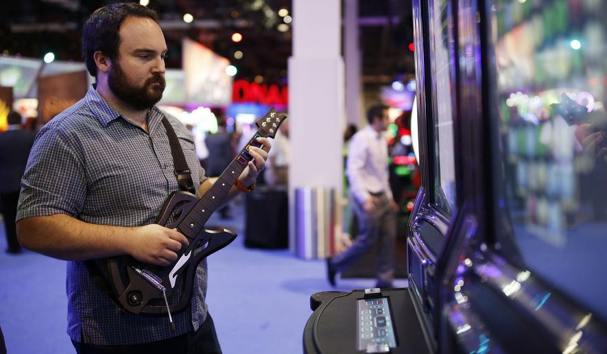 "FILE - In this Sept. 30, 2015, file photo, Brett Boge of Reno, Nev., plays Guitar Warrior by G2 Game Design during the Global Gaming Expo in Las Vegas. Massachusetts Gaming Commission members met on Thursday, Feb. 18, 2016, to discuss draft regulations for so-called ""skill-based"" slot machines that incorporate video game and arcade-like elements, meant to appeal to millennials who skip over traditional slot machines they see as old-fashioned. (AP Photo/John Locher, File)"