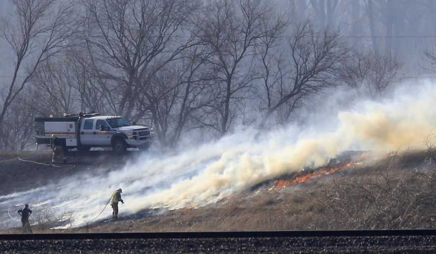 Firefighters battle a wildfire near Beverly, Mo., Thursday, Feb. 18, 2016. (AP Photo/Orlin Wagner)