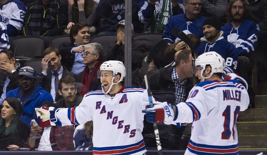 New York Rangers center Derek Stepan, left, celebrates his goal against the Toronto Maple Leafs with teammate J.T. Miller (10) during the third period of an NHL hockey game Thursday, Feb. 18, 2016, in Toronto. (Nathan Denette/The Canadian Press. via AP)