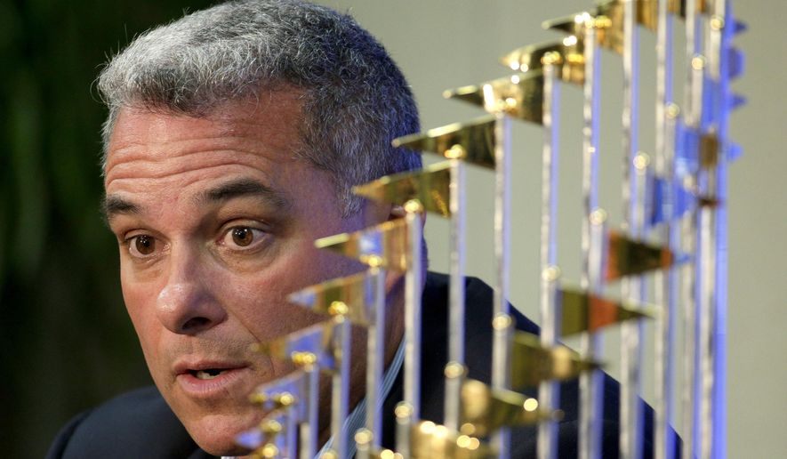 FILE - IN this Nov. 5, 2015, file photo, Kansas City Royals general manager Dayton Moore speaks to members of the media along side the Royals' World Series trophy during a news conference wrapping up the team's season, in Kansas City, Mo. The Royals have signed general manager Dayton Moore and manager Ned Yost to contract extensions, ensuring that the leadership of the World Series champions will remain intact. (AP Photo/Charlie Riedel, File)