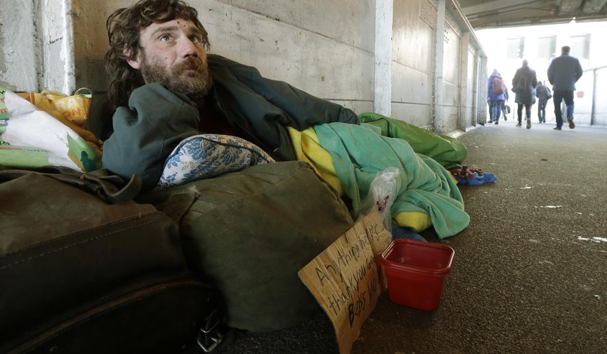 Harold McDuffie II, who says he has been homeless for three years, lies in a sleeping bag on a pedestrian bridge leading to the ferry dock in downtown Seattle on Tuesday, Feb. 9, 2016. Ten years ago, a coalition of leaders came up with a plan to end homelessness by 2015. In that time, the city and county built more than 6,300 housing units and helped nearly 40,000 people find homes. Yet the number of homeless people has continued to climb. (AP Photo/Ted S. Warren)