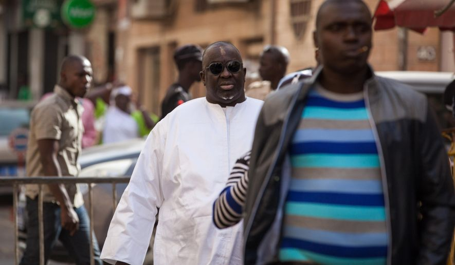 Papa Massata Diack, centre, son of former IAAF President Lamine Diack arrives at the central police station in Dakar, Senegal, Monday,  Feb. 17, 2016.   Diack is accused of money laundering and alleged corruption and is wanted by French prosecutors. (AP Photo/Vincent Tremeau)