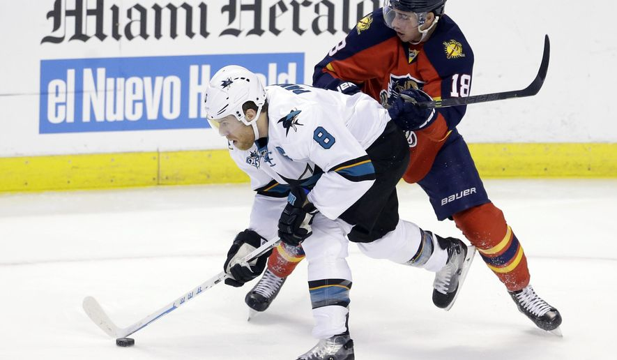 San Jose Sharks center Joe Pavelski (8) skates with the puck as Florida Panthers right wing Reilly Smith (18) defends during the first period of an NHL hockey game, Thursday, Feb. 18, 2016, in Sunrise, Fla. (AP Photo/Alan Diaz)