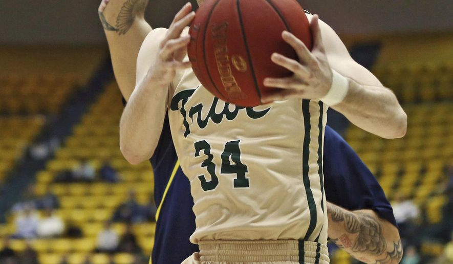 William & Mary's David Cohn (34) prepares to shoot the ball as UNC Wilmington's Marcus Bryan (21) defends during an NCAA college basketball game in Williamsburg, Va., on Thursday, Feb. 18, 2016. (Aileen Devlin/The Daily Press via AP) MANDATORY CREDIT