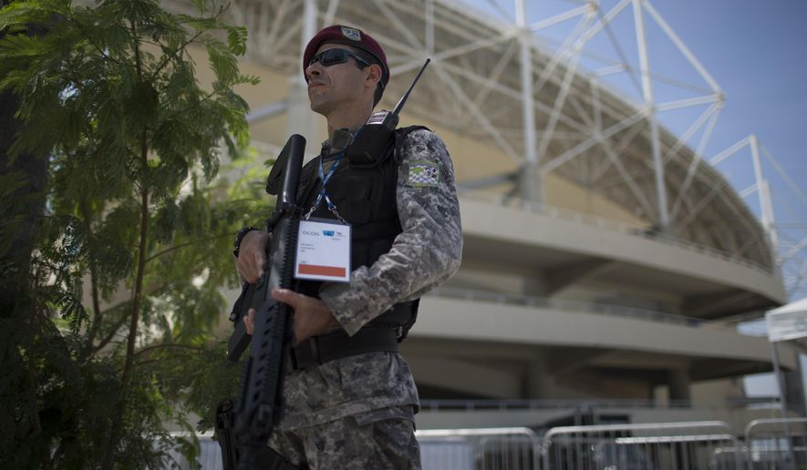 A police officer stands guard in front of the Maria Lenk Aquatics Center, at the Olympic Park in Rio de Janeiro, Brazil, Friday, Feb. 19, 2016. More than 280 security personnel are in place to safeguard the Aquatics Center, athletes, and public attending the ongoing FINA World Diving Cup. The security operation is also part practice for the Rio 2016 Olympic Games. (AP Photo/Leo Correa)