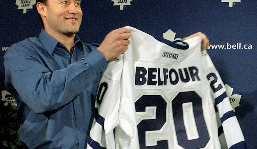 FILE - In this July 3, 2002, new Maple Leafs goaltender Ed Belfour receives his number 20 jersey at a news conference in Toronto. Ed Belfour is preparing to give up his Olympic gold medal for an opportunity to go into business with his son. The medal the Hockey Hall of Fame goalie won representing Canada at the 2002 Salt Lake City Games is one of 66 pieces of personal NHL memorabilia Belfour has put up for auction. (AP Photo/J.P. Moczulski, File)