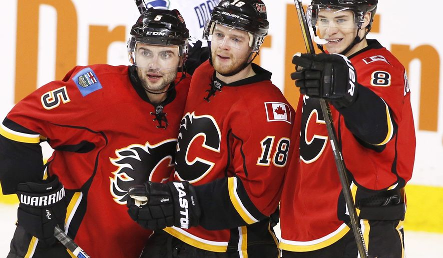 Calgary Flames' Mark Giordano, left, Matt Stajan, center, and Joe Colborne celebrate Michael Frolik's goal against the Vancouver Canucks during the second period of an NHL hockey game Friday, Feb. 19, 2016, in Calgary, Alberta. (Larry MacDougal/The Canadian Press via AP)