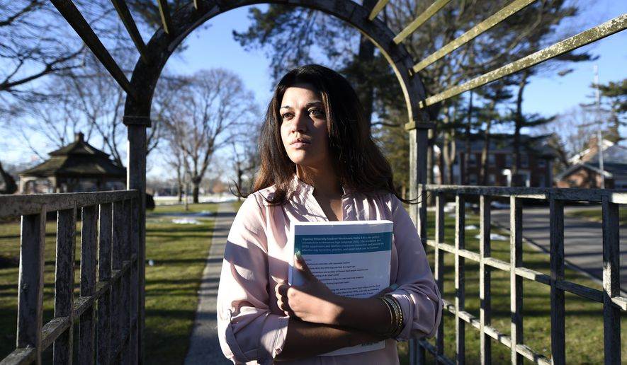 In this Feb. 2, 2016 photo, Naila Amin, 26, holds a book from one of the classes she is taking at Nassau Community College in Garden City, N.Y. Amin, who was forced into marriage at the age of 15 to a 28-year-old cousin in Pakistan who beat and mistreated her, aspires to become a social worker and open a group home for girls trying to avoid or recover from forced marriages. (AP Photo/Kathy Kmonicek)