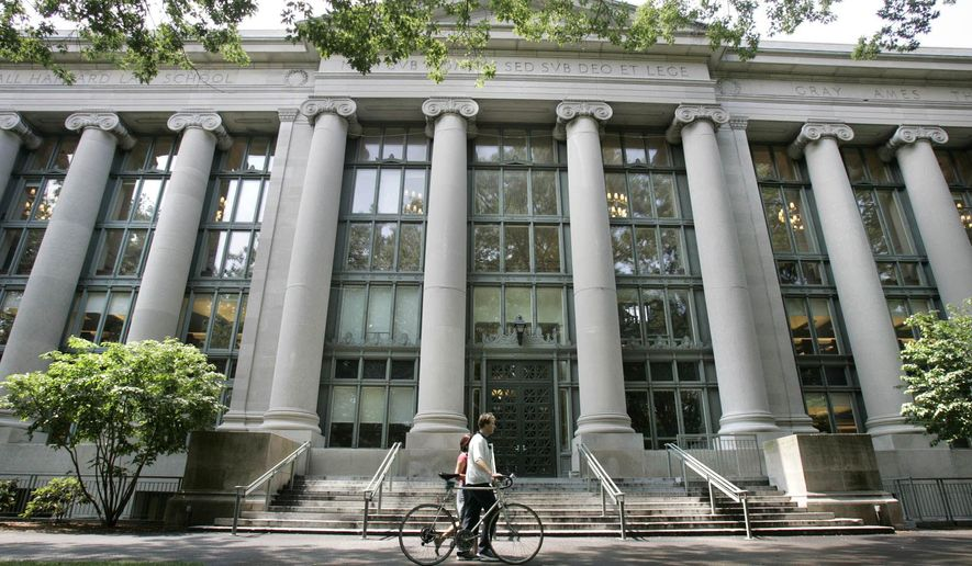 In this Aug. 1, 2005, file photo, a bicyclist walks by Harvard University's Langdell Hall, which includes Harvard Law School's library, in Cambridge, Mass. (AP Photo/Charles Krupa, File)