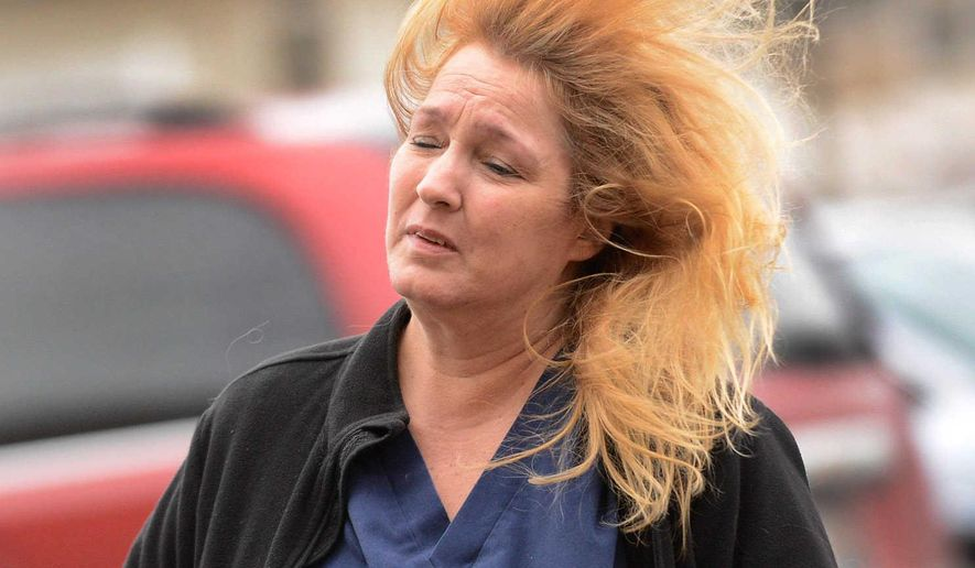 Gail Becker, of Lombard, Ill., struggles in the wind in the parking lot of Ultra Fresh Foods in Lombard, Ill., Friday, Feb. 19, 2016, as high winds impacted the suburbs of Chicago. (Bob Chwedyk/Daily Herald via AP) MANDATORY CREDIT; MAGS OUT, TV OUT  MBI