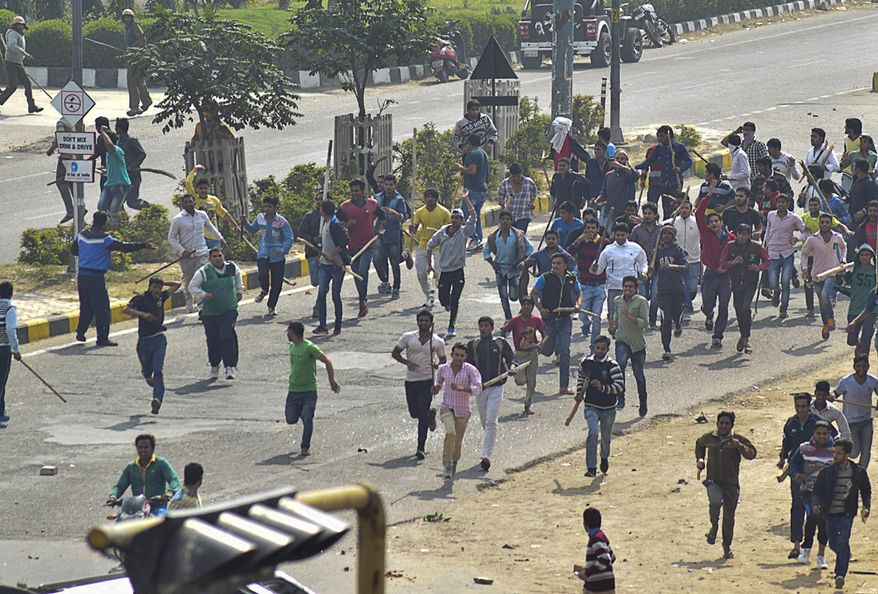 Protesters run some with sticks  during a pro caste quota protest in Rohtak, 70 kilometers (45 miles) west of New Delhi, India, Friday, Feb. 19, 2016.  India's paramilitary forces shot and killed one person on Friday as protests for government benefits turned violent in northern India, police said. Thousands of people belonging to the Jat agricultural community were protesting in Rohtak and other towns in Haryana state, to demand an increase in their caste quota benefits, which include guaranteed government jobs or university spots. (AP Photo/Deepak Khanna)  NO ARCHIVES NO SALES