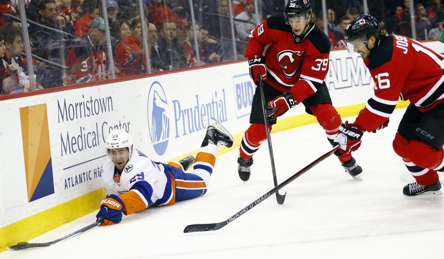 New York Islanders defenseman Nick Leddy, left, dives for the puck as New Jersey Devils defenseman Seth Helgeson (39) and center Jacob Josefson (16), of Sweden, defend during the first period of an NHL hockey game, Friday, Feb. 19, 2016, in Newark, N.J. (AP Photo/Julio Cortez)
