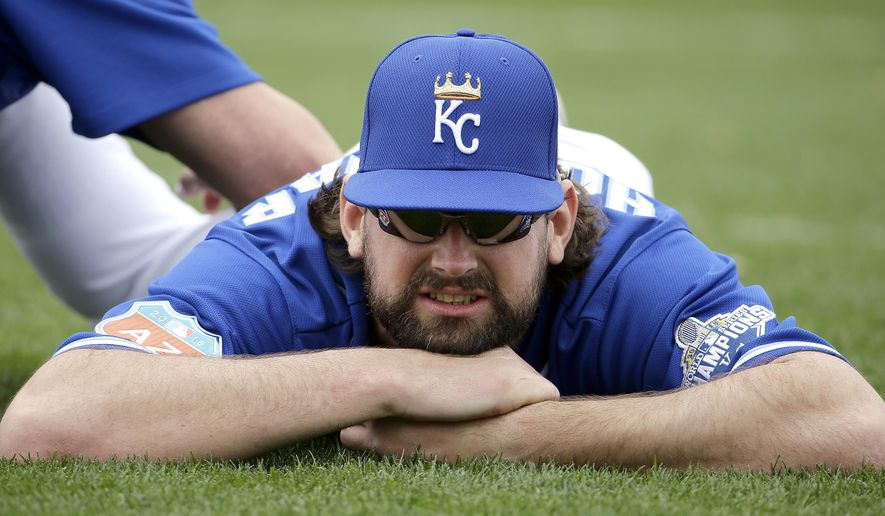 Kansas City Royals relief pitcher Luke Hochevar is worked on by a trainer during spring training baseball practice Friday, Feb. 19, 2016, in Surprise, Ariz. (AP Photo/Charlie Riedel)