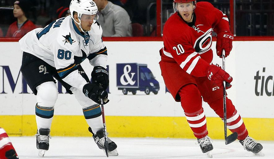 Carolina Hurricanes' Riley Nash (20) works the puck on San Jose Sharks' Matt Tennyson (80) during the first period of an NHL hockey game Friday, Feb. 19, 2016, in Raleigh, N.C. (AP Photo/Karl B DeBlaker)