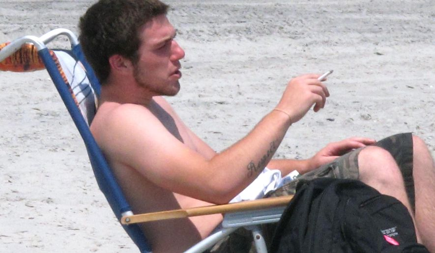 In this July 23, 2014 photo, a man smokes a cigarette on the beach in Atlantic City, N.J. New Jersey is trying again to enact a ban on smoking at public beaches and parks, but the measure would allow up to 15 percent to be set aside as a designated smoking area. Gov. Chris Christie vetoed an identical bill in 2014.(AP Photo/Wayne Parry)