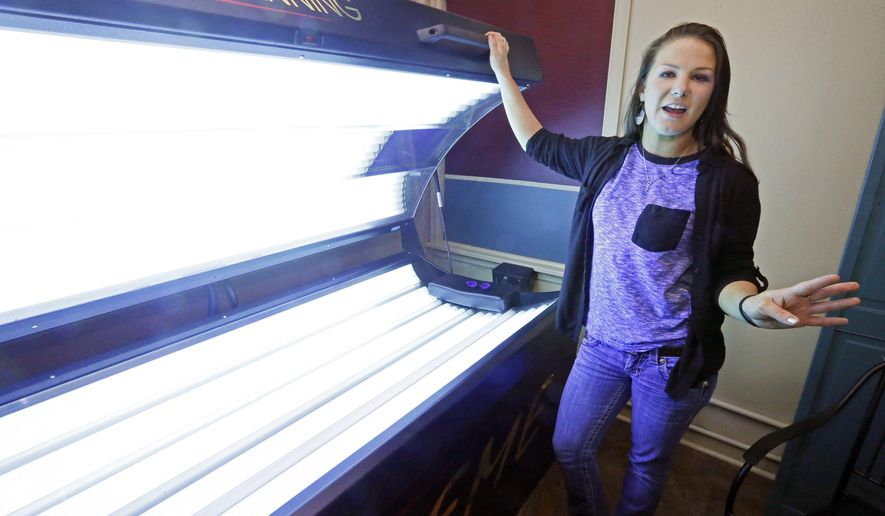 Linzy Rayfield, manager of Sun Gallery Tanning Studio in Ridgeland, Miss., stands at a level three tanning bed as she explains the company's safety steps Friday, Feb. 19, 2016. The Mississippi Dermatology Association, Mississippi State Department of Health and the American Cancer Society, citing health risks, have joined in an effort get lawmakers to support legislation that would ban anyone under age 18 from using indoor tanning beds and lamps even once. (AP Photo/Rogelio V. Solis)