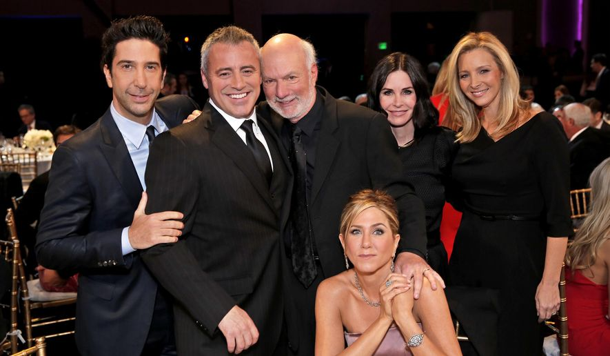 "In this image released by NBC, director James Burrows, standing center, poses with the cast of ""Friends,"" from left,  David Schwimmer, Matt LeBlanc, Jennifer Aniston, seated, Courteney Cox and Lisa Kudrow during the taping of ""Must See TV: An All-Star Tribute to James Burrows,"" airing Sunday at 9 p.m. EST on NBC.  (Chris Haston/NBC via AP)"