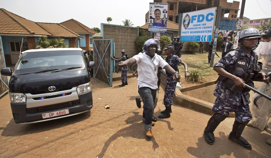 A plain-clothes policeman shouts to the media to get away as a black-windowed police van believed to contain arrested opposition leader Kizza Besigye speeds away under a police escort, at his party headquarters in Kampala, Uganda, Friday, Feb. 19, 2016. Police in Uganda arrested opposition leader Kizza Besigye at his party's headquarters Friday after heavily armed police surrounded the building and fired tear gas and stun grenades at his supporters who took to the streets. (AP Photo/Ben Curtis)