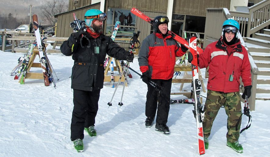 Military veterans Bryan Ashley-Selleck, left, Roger Bushey, center, and Tyler Arel, who suffer post-traumatic stress disorder, skiing together at Bolton Valley Resort in Bolton, Vt,, Thursday Feb. 18, 2016.  A group of service members of the Gulf, Iraq and Vietnam wars say the weekly gatherings through the Vermont Adaptive Ski & Sport programs help get them out of the house, connect with other people and take their mind off of their post-traumatic symptoms. (AP Photo/Lisa Rathke)