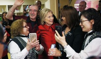 Democratic presidential candidate Hillary Clinton, reacts as employees of Harrah's Las Vegas surround her during a visit to the hotel and casino on the day of the Nevada Democratic caucus, Saturday, Feb. 20, 2016, in Las Vegas. (AP Photo/John Locher)