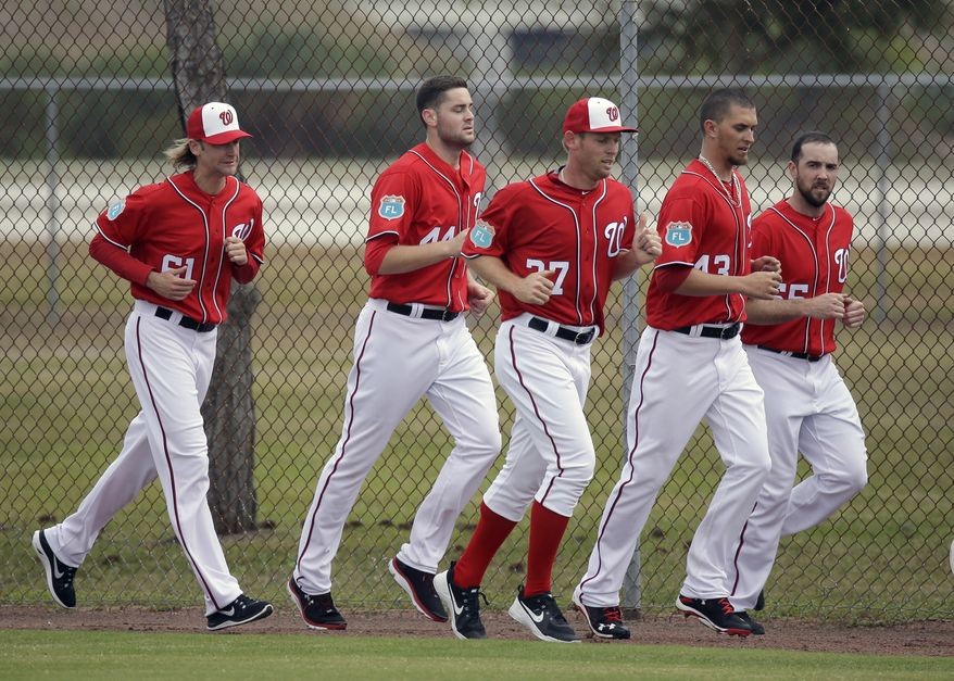 Washington Nationals pitchers, from left, Bronson Arroyo, Lucas Giolito, Stephen Strasburg,  A.J. Cole and Taylor Hill run sprints after a spring training baseball workout, Saturday, Feb. 20, 2016, in Viera, Fla. (AP Photo/John Raoux)