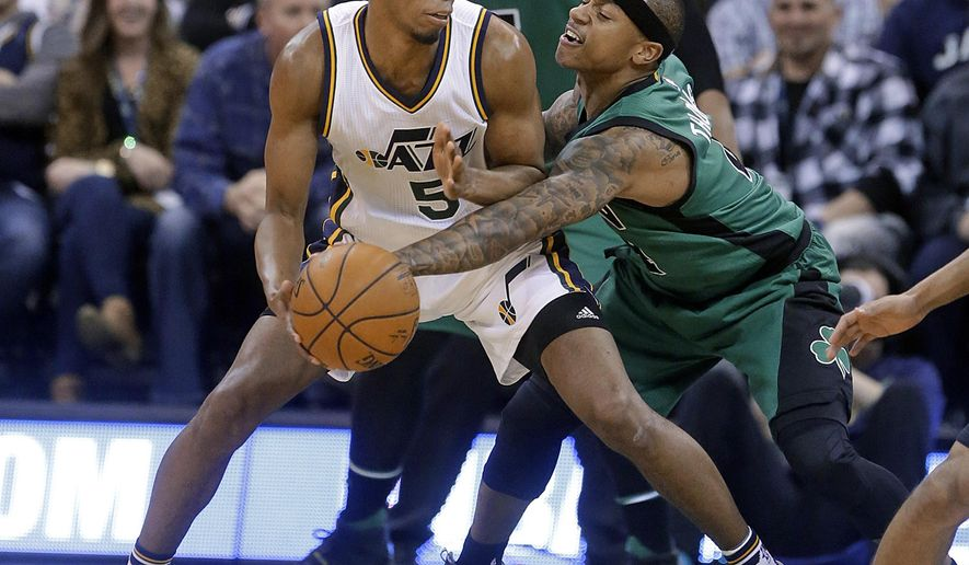 Boston Celtics guard Isaiah Thomas, right, reaches for the ball as Utah Jazz guard Rodney Hood (5) drives during the second quarter of an NBA basketball game Friday, Feb. 19, 2016, in Salt Lake City. (AP Photo/Rick Bowmer)