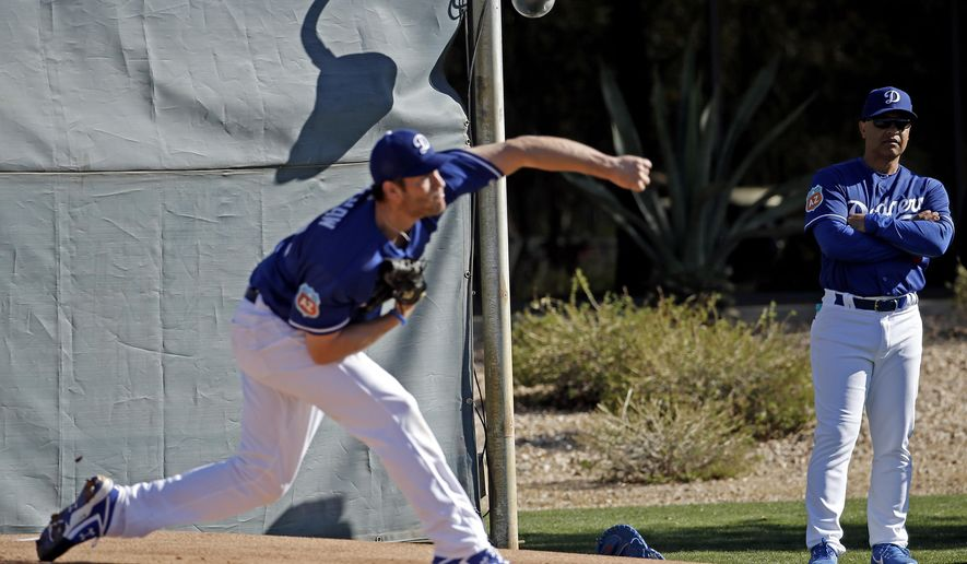 Los Angeles Dodgers manager Dave Roberts watches as Clayton Kershaw throws during a spring training baseball workout Saturday, Feb. 20, 2016, in Glendale, Ariz. (AP Photo/Morry Gash)