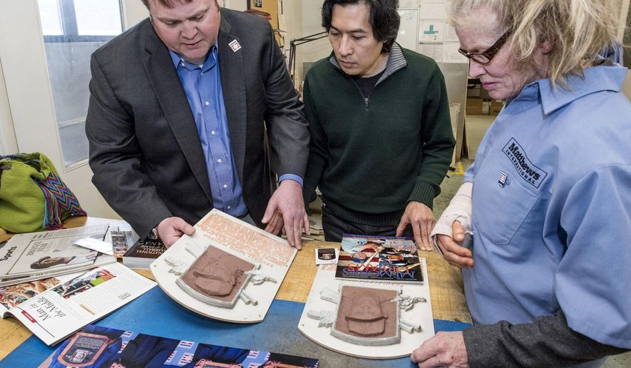 In this Jan. 27, 2016, photo provided by Matthews International Corp., the company's sales and marketing director for sports and entertainment Josh Rooney, left, and sculptors Tom Tsuchiya, center, and Mindy Ellis, right, examine molds for plaques of Baseball Hall of Fame inductees Craig Biggio and Randy Johnson, at the company's facility in Pittsburgh. For over three decades, Matthews International Corp. has produced plaques for the Baseball Hall of Fame in Cooperstown, N.Y. (Matthews International Corp. via AP)