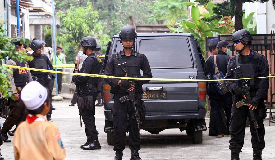 Indonesian police officers stand guard outside the house of a suspected militant following a raid in Malang, Indonesia, Saturday, Feb. 20, 2016. The police arrested a number of people allegedly linked to Jan. 14 attack in Jakarta, in a series of raids in the East Java city Saturday. (AP Photo/H.Y. Prabowo)