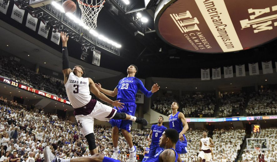 Texas A&M's Admon Gilder (3) makes a basket as Kentucky's Tyler Ulis (3) falls to the ground during the first half of an NCAA college basketball game, Saturday, Feb. 20, 2016, in College Station, Texas. (AP Photo/Sam Craft)