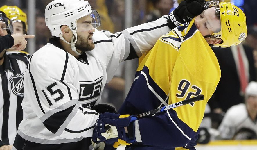 Los Angeles Kings forward Andy Andreoff (15) scuffles with Nashville Predators center Ryan Johansen (92) in the first period of an NHL hockey game Saturday, Feb. 20, 2016, in Nashville, Tenn. Andreoff was penalized for roughing. (AP Photo/Mark Humphrey)