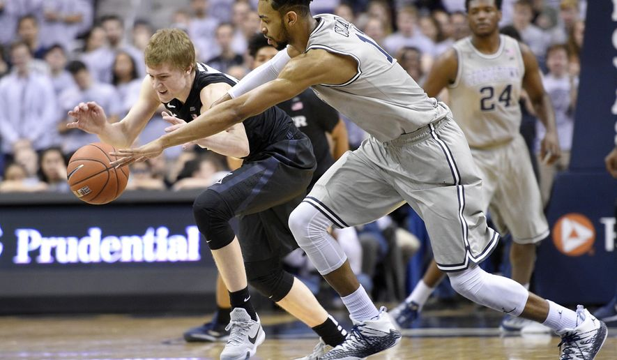 Georgetown forward Isaac Copeland, front, battles for a loose ball against Xavier guard J.P. Macura, left, during the first half of an NCAA college basketball game, Saturday, Feb. 20, 2016, in Washington. (AP Photo/Nick Wass)
