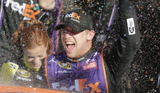 Denny Hamlin celebrates in Victory Lane after winning the NASCAR Daytona 500 Sprint Cup Series auto race at Daytona International Speedway in Daytona Beach, Fla., Sunday, Feb. 21, 2016. (AP Photo/Terry Renna)