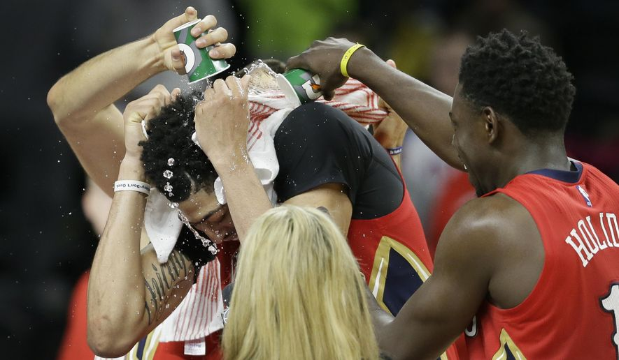 New Orleans Pelicans guard Jrue Holiday and a teammate pour water on forward Anthony Davis after an NBA basketball game against the Detroit Pistons, Sunday, Feb. 21, 2016, in Auburn Hills, Mich. The Pelicans won 111-106. (AP Photo/Carlos Osorio)