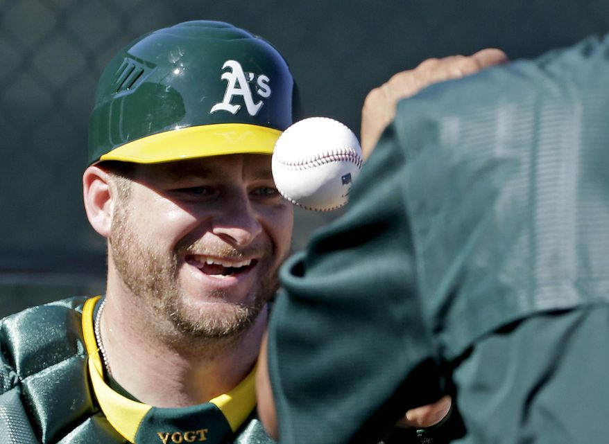 Oakland Athletics catcher Stephen Vogt works on a drill during spring training baseball practice in Mesa, Ariz., Sunday, Feb. 21, 2016. (AP Photo/Chris Carlson)