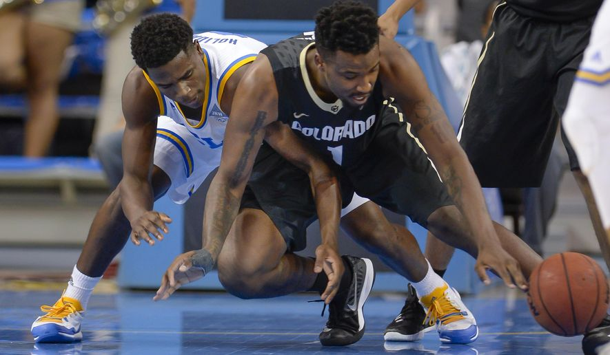 UCLA guard Aaron Holiday, left and Colorado forward Wesley Gordon (1) reach for a loose ball during the first half of an NCAA college basketball game Saturday, Feb. 20, 2016, in Los Angeles. (AP Photo/Gus Ruelas)