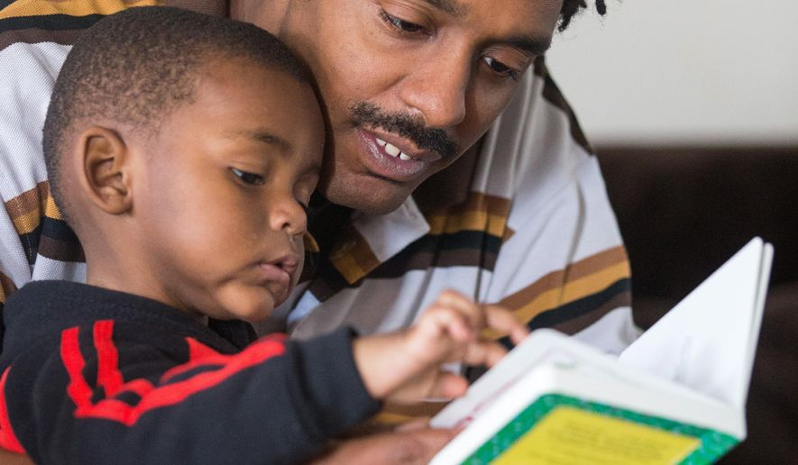 ADVANCE FOR WEEKEND EDITIONS, SATURDAY, FEB. 20- SUNDAY, FEB. 21, 2016-  In this photo taken on Wednesday, Jan. 27, 2016, Ricky Lessley reads to his son, Ricky Lesley at their home in Omaha, Neb. The Learning Community is dispatching home visitors to instruct low-income parents on how to interact with their infants and toddlers. (Matt Dixon /Omaha World-Herald via AP) MAGS OUT; ALL NEBRASKA LOCAL BROADCAST TELEVISION OUT; MANDATORY CREDIT