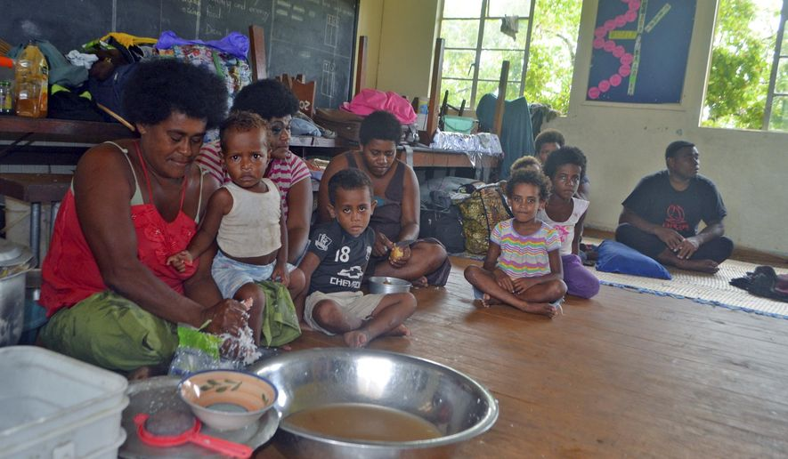 Families from Wainiveidilo settlement prepare their lunch at a school used as an evacuation center in Navua, Fiji, Sunday, Feb. 21, 2016, after cyclone Winston ripped through the country. Officials in Fiji are assessing damage in the wake of the ferocious cyclone that tore through the Pacific island chain. (Jonacani Lalakobau/Fiji Times via AP) EDITORIAL USE ONLY, FIJI OUT