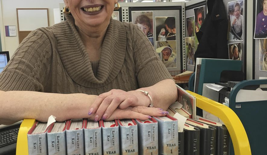Carrie Ingle, 77, poses at her desk at the Columbus Metropolitan Library Operations Center in Columbus, Ohio, on Thursday, Feb. 18, 2016. Ingle has worked for the library for six decades. Sixty years have come and gone, and Ingle still is working full time behind the scenes, still surrounded each day by stacks of brand new books in what is now one of the busiest big-city library systems in the country. (AP Photo/Mitch Stacy)