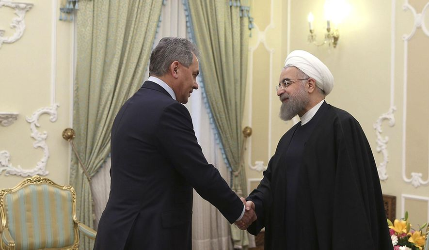 In this photo released by official website of the office of the Iranian Presidency, President Hassan Rouhani, right, shakes hands with Russian Defence Minister Sergei Shoigu at the start of their meeting in Tehran, Iran, Sunday, Feb. 21, 2016. (Iranian Presidency Office via AP)
