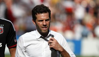 D.C. United head coach Ben Olsen, loosens his tie after an MLS soccer match against the New York Red Bulls, at RFK Stadium, Sunday, Aug. 31, 2014, in Washington. United won 2-0. (AP Photo/Alex Brandon)